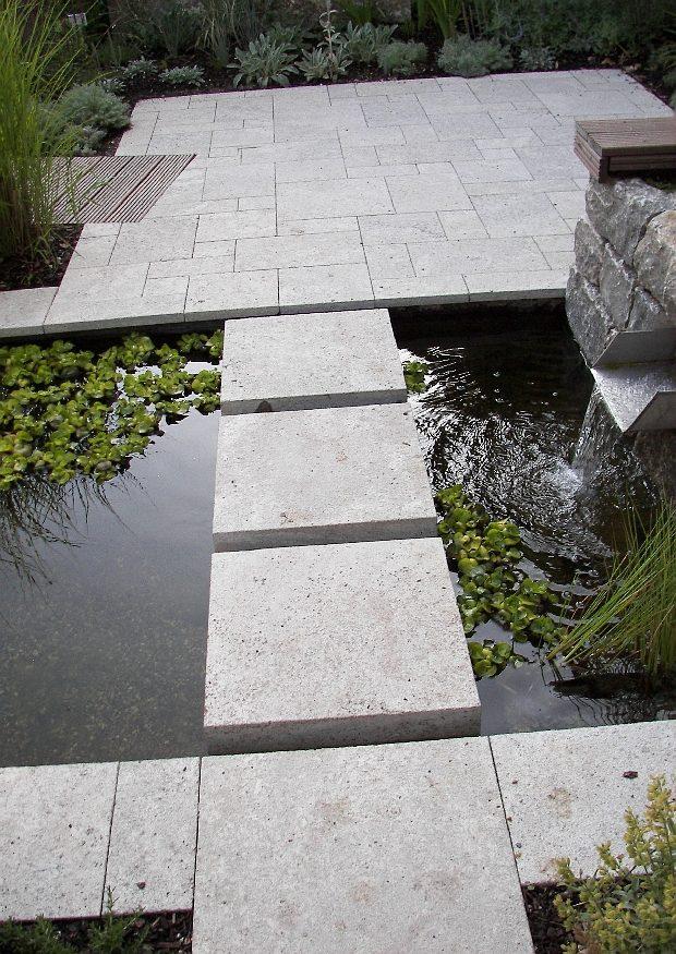 Gartengestaltung mit Natursteinplatten in einem Wasserbecken
