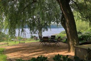 Urlaubsgartenpflege - Hängeweide über Sitzplatz mit Schaukel