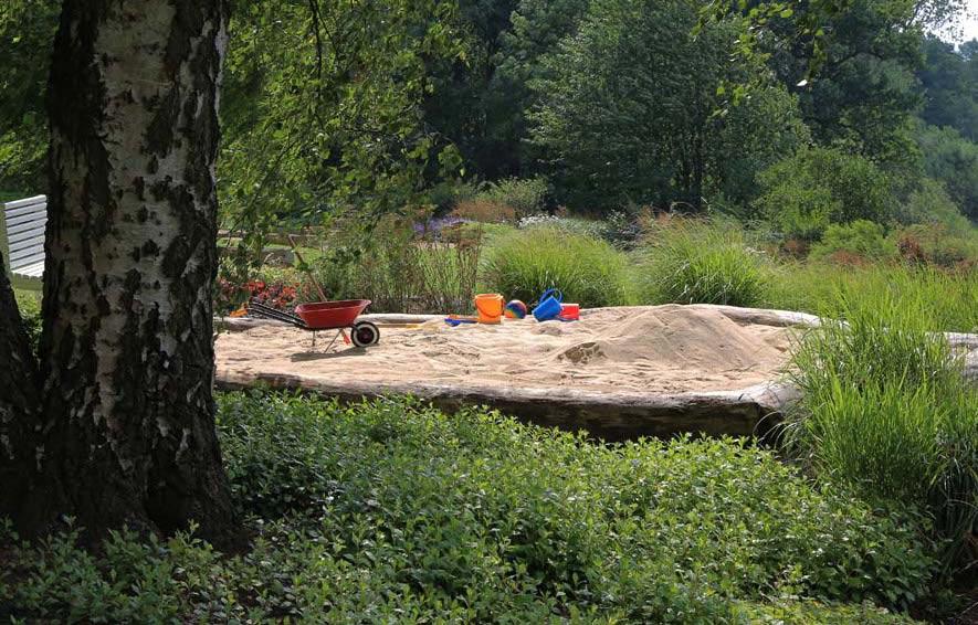 Sandkiste eingefasst mit Baumstämmen